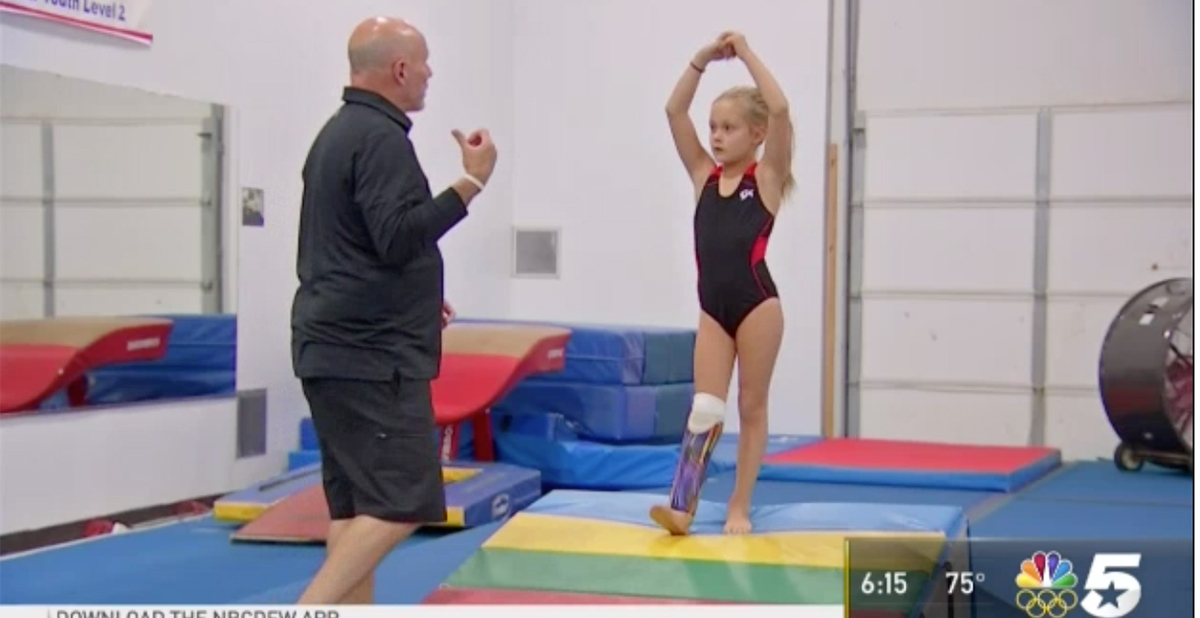 Gymnastics coach instructs Aspen