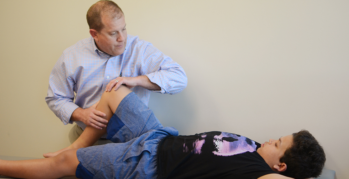 Chuck examines a patient's knee.