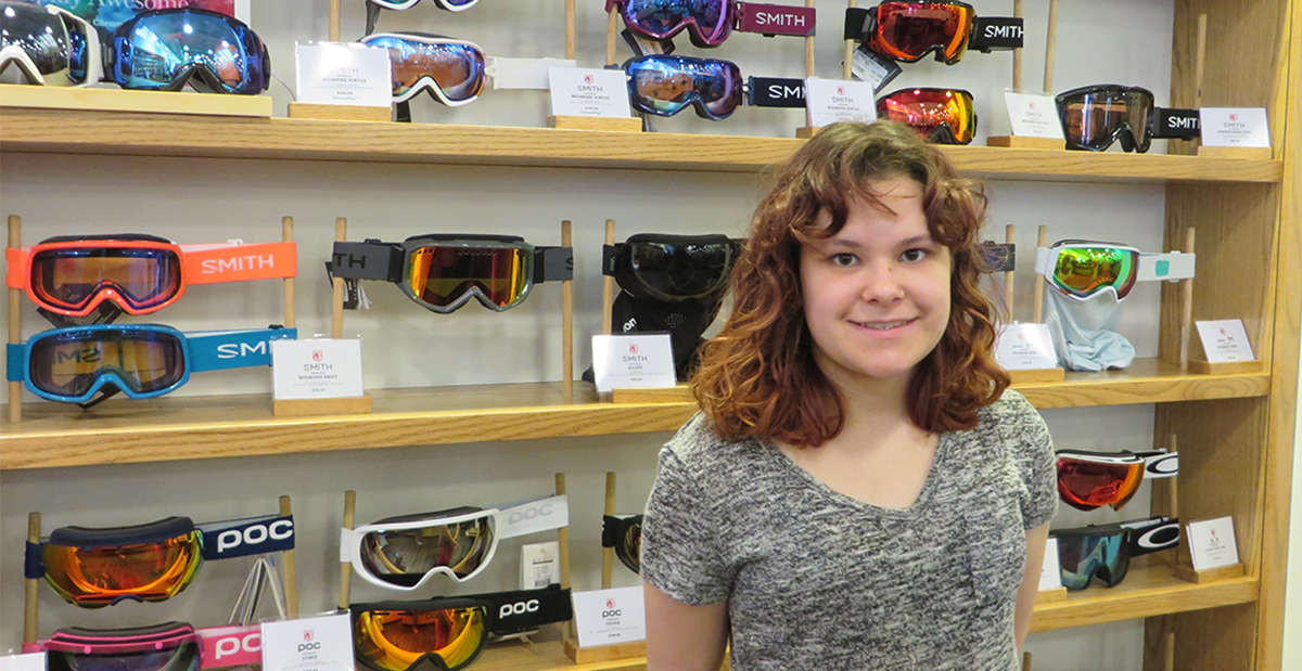 cydney standing in front of a wall of goggles at saint bernard sports