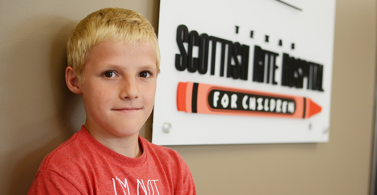 Young boy in front of Scottish Rite Hospital sign.
