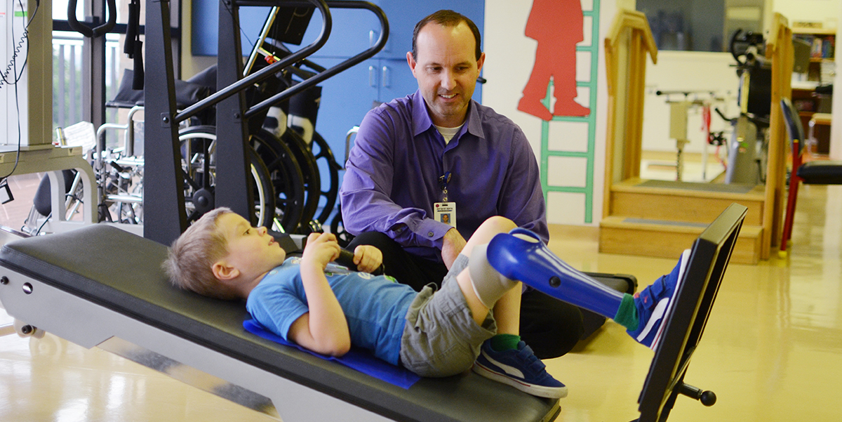 A physical therapist helps a patient during a therapy session.