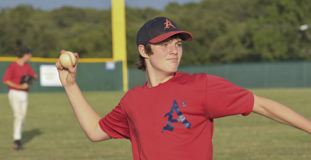 Teenage boy throwing a pitch at a baseball game.