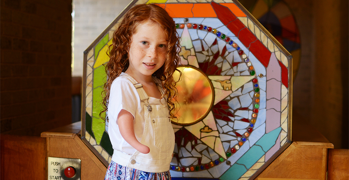 young girl with red hair standing in front of stained glass