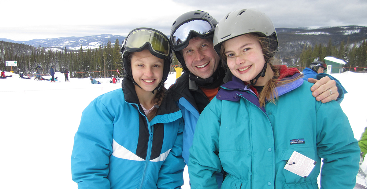 Dr. Ellis on the ski slopes with two patients.