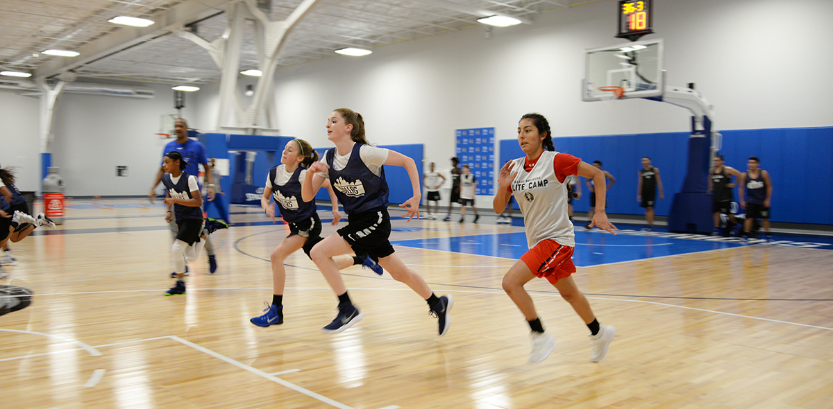 Young athletes running in basketball practice.