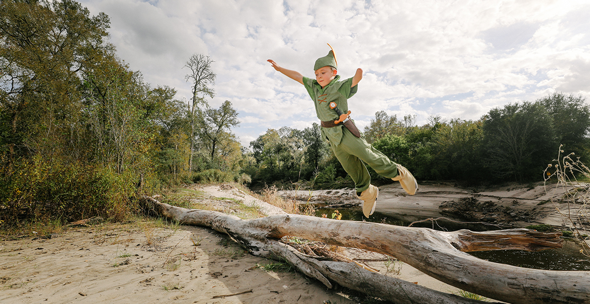 Miles as Peter Pan jumping off tree trunk