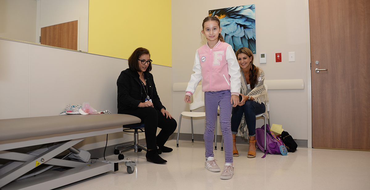 orthopedic shoes girl walking in exam room with mom and nurse behind her