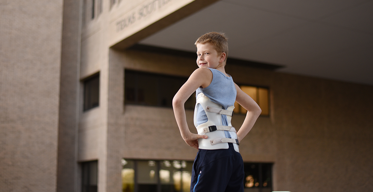 child in brace outside hospital