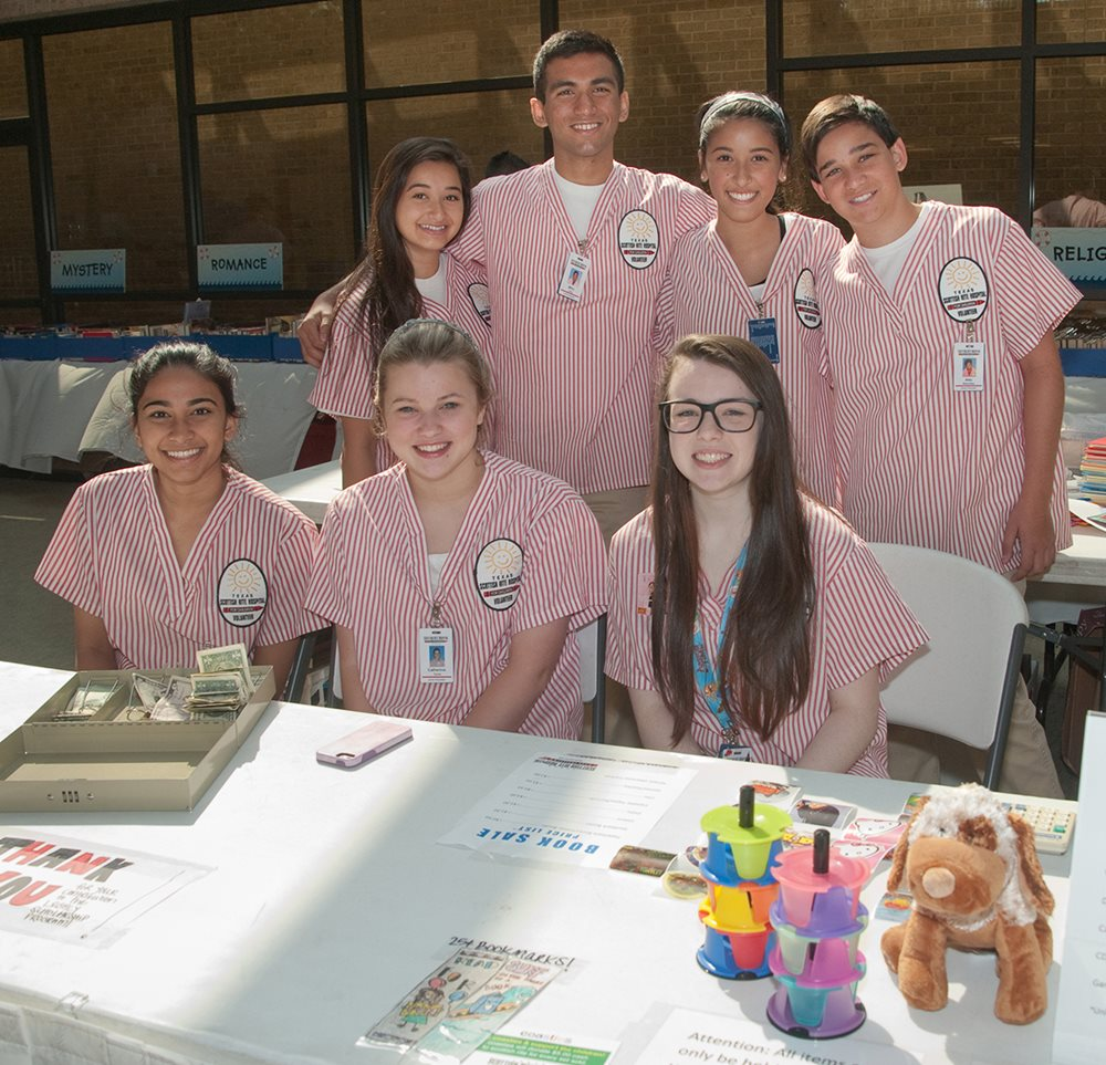 Junior volunteers helping at Texas Scottish Rite Hospital for Children book sale event