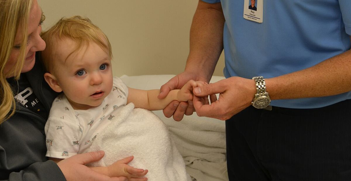 Doctor examines child's hand