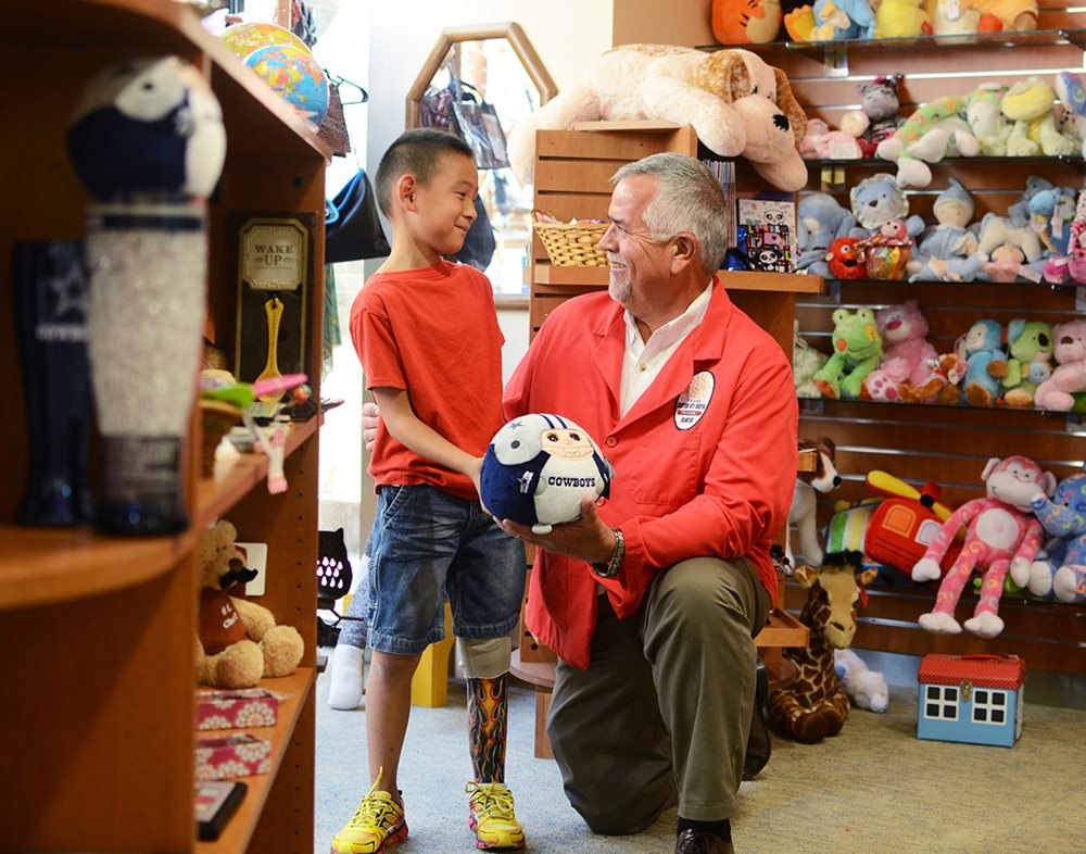Volunteer with young boy with prosthetic leg at Scottish Rite Hospital gift shop