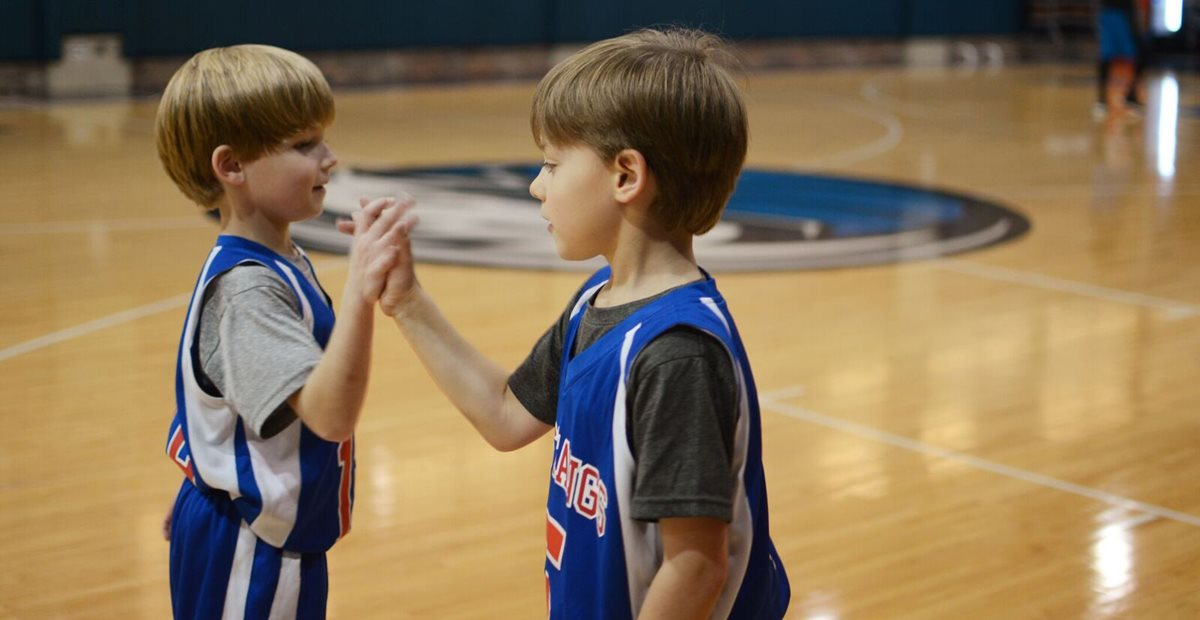 Children on basketball court give each other high fives