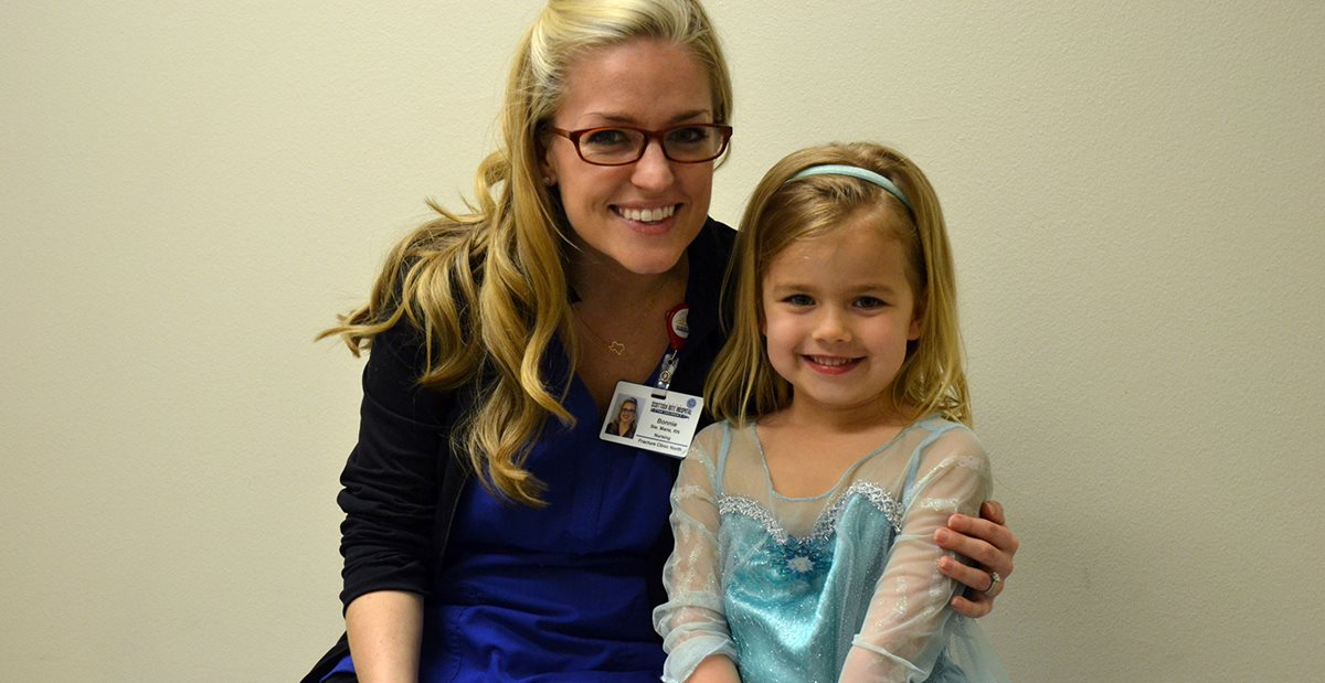 Nurse at the Texas Scottish Rite Hospital for Children Fracture Clinic assists small girl dressed as princess