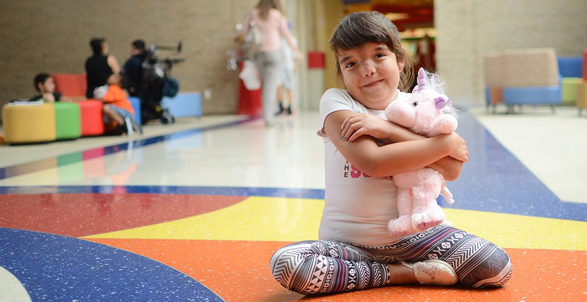 Child with magnetic spinal rods holds toy at Texas Scottish Rite Hospital for Children