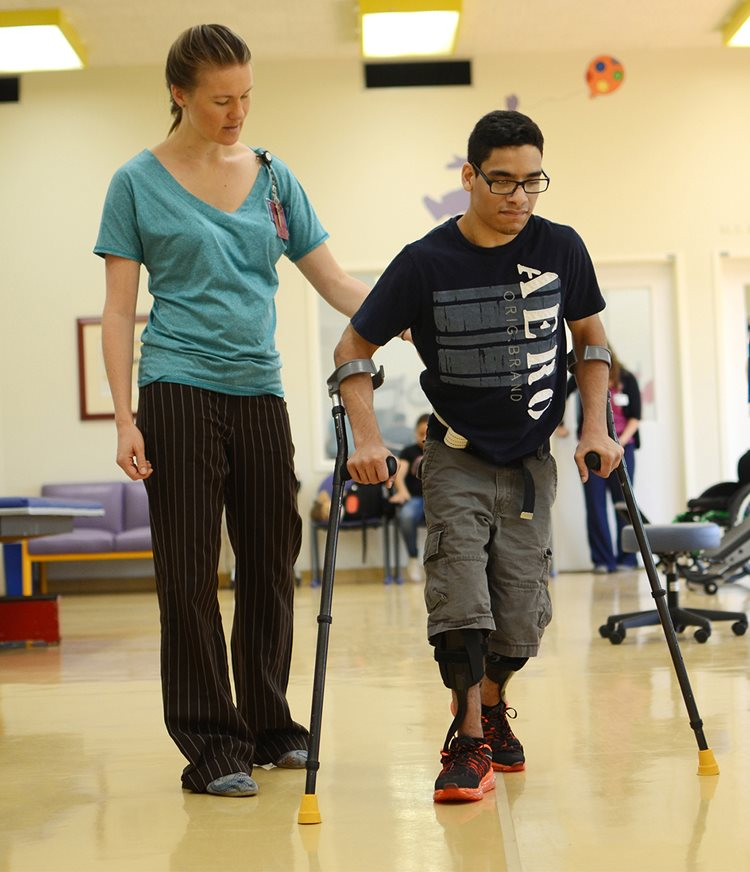 Physical therapist helping patient with forearm crutches walk at Texas Scottish Rite Hospital for Children