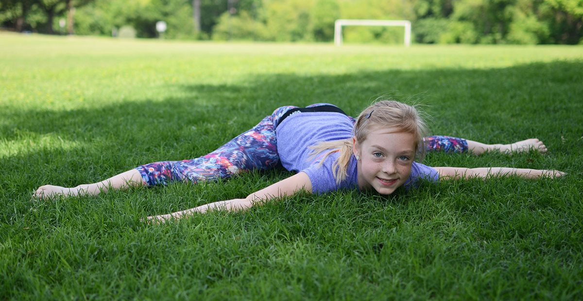 Child stretches on a soccer field