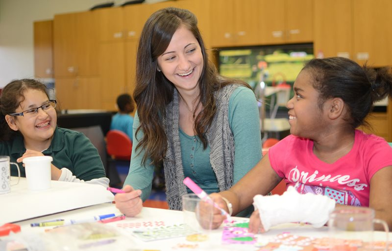 Child Life Specialist and patients smiling while coloring at Texas Scottish Rite Hospital for Children