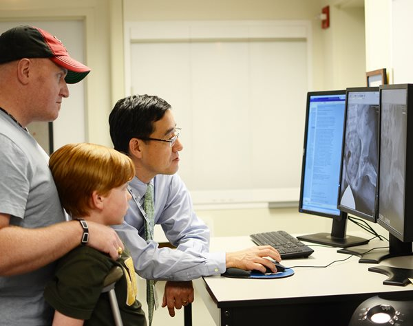 Pediatric orthopedic hip surgeon reviewing X-rays with patient at Center for Excellence in Hip at Texas Scottish Rite Hospital for Children