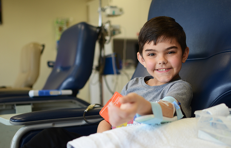Pediatric rheumatology patient smiling during visit at Texas Scottish Rite Hospital for Children