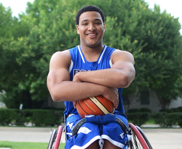 Teenage boy in wheelchair playing in basketball league provided by the Therapeutic Recreation department at Texas Scottish Rite Hospital for Children