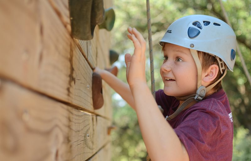 Young boy rock climbing at Texas Scottish Rite Hospital for Children recreational camp