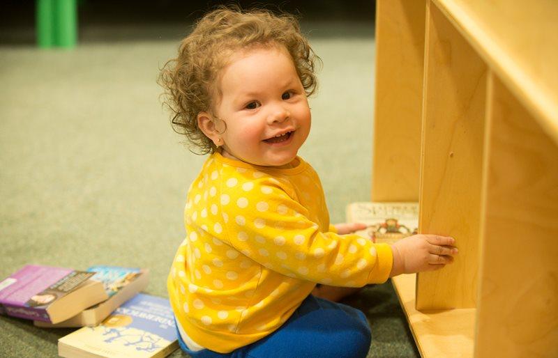 Smiling toddler playing with books at Family Resource Center at Texas Scottish Rite Hospital for Children