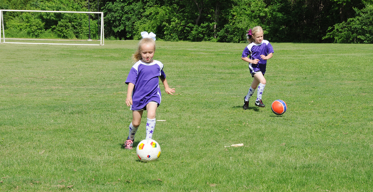 Two young girls playing soccer outside.
