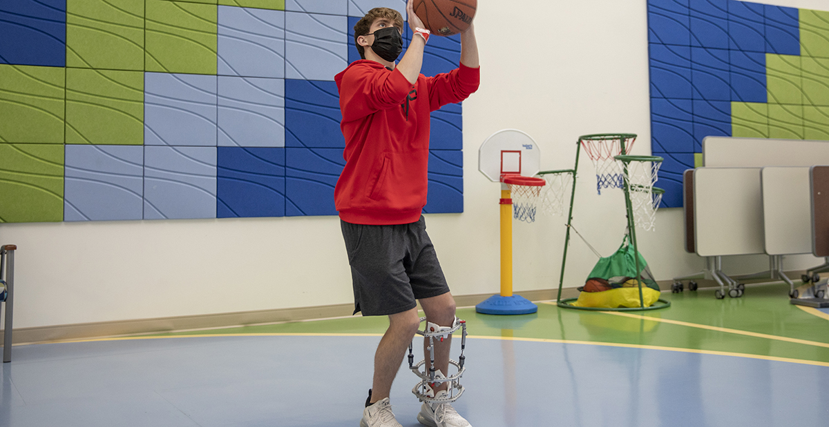 patient in a limb lengthening frame playing basketball