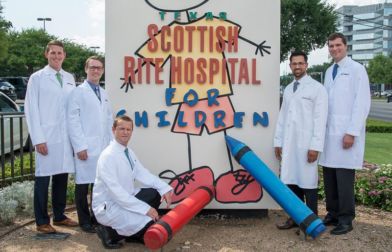 Members of the fellowship program pose in front of the Texas Scottish Rite Hospital for Children sign