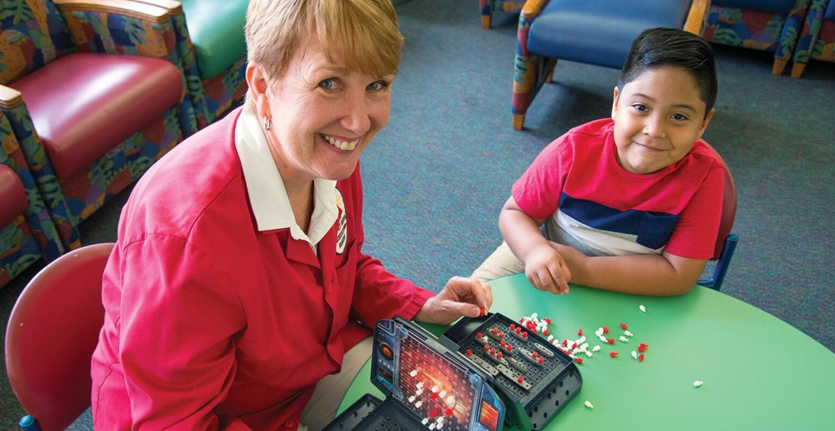 Texas Scottish Rite Hospital for Children volunteer plays with patient