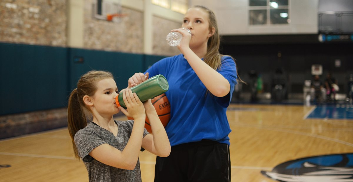 Young athletes drinking water on a basketball court