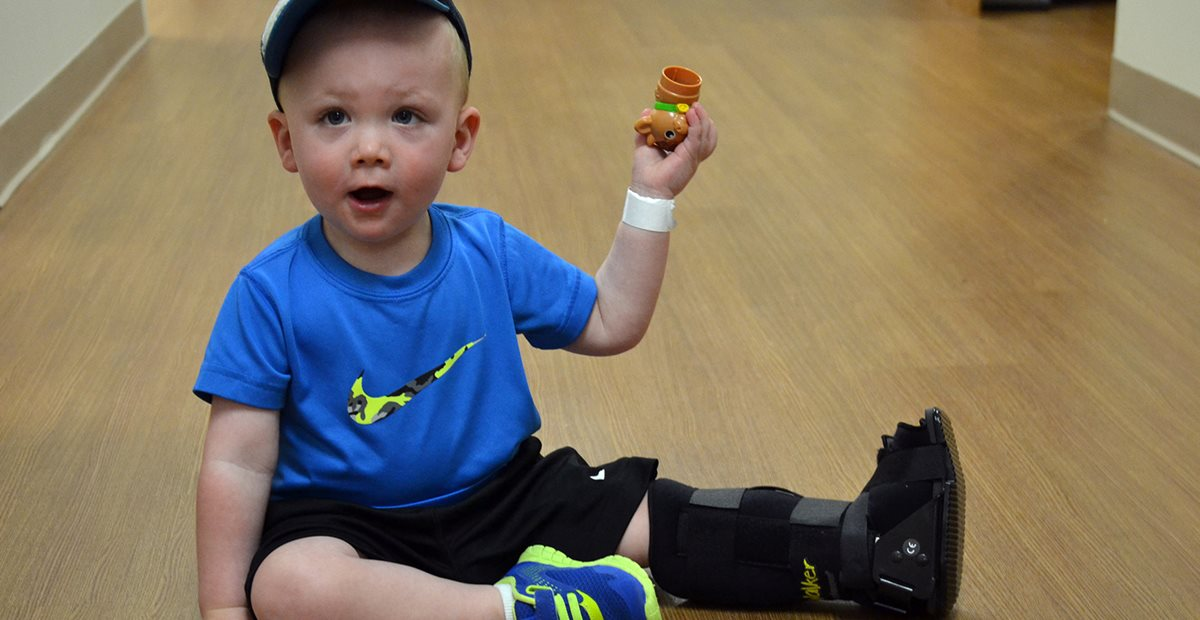 Toddler with a broken foot plays with toys