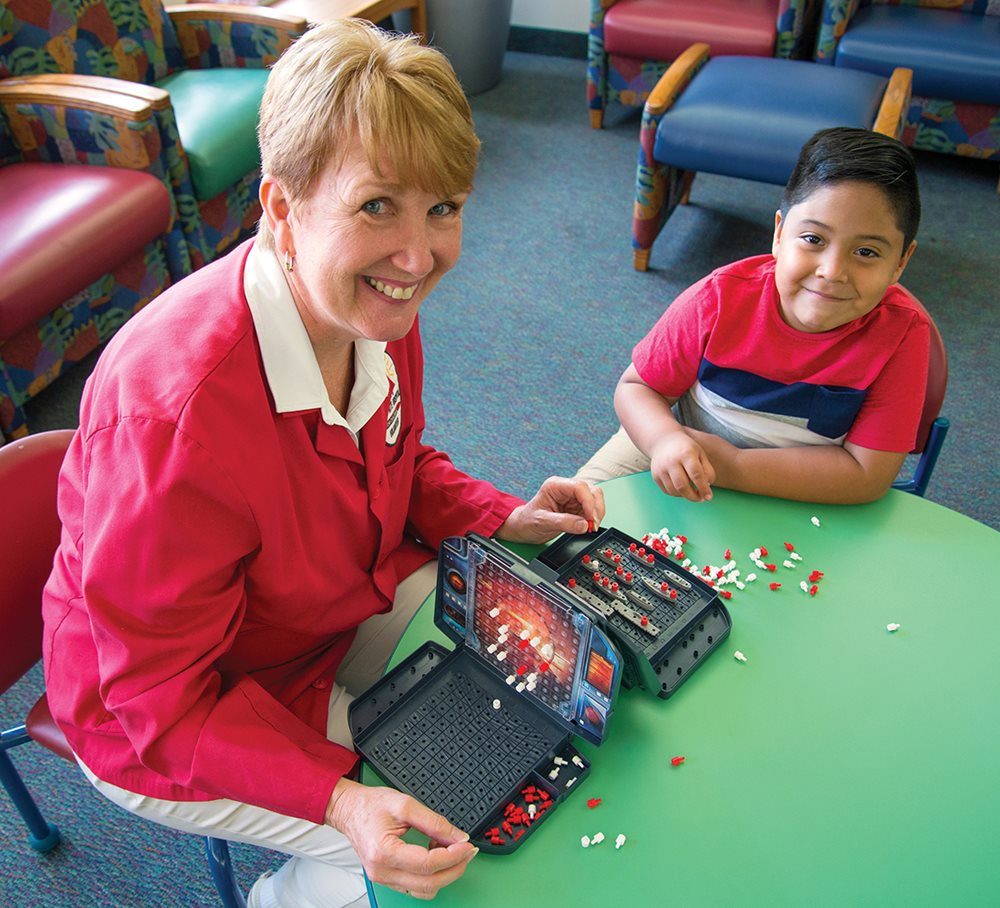 Adult volunteer playing Battleship with young boy at Texas Scottish Rite Hospital for Children