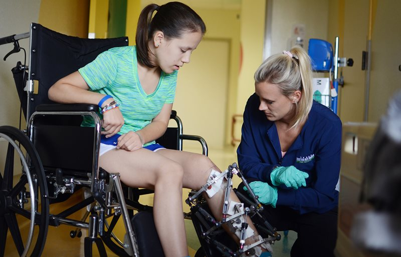 Nurse attending to patient recovering from limb lengthening surgery at Texas Scottish Rite Hospital for Children