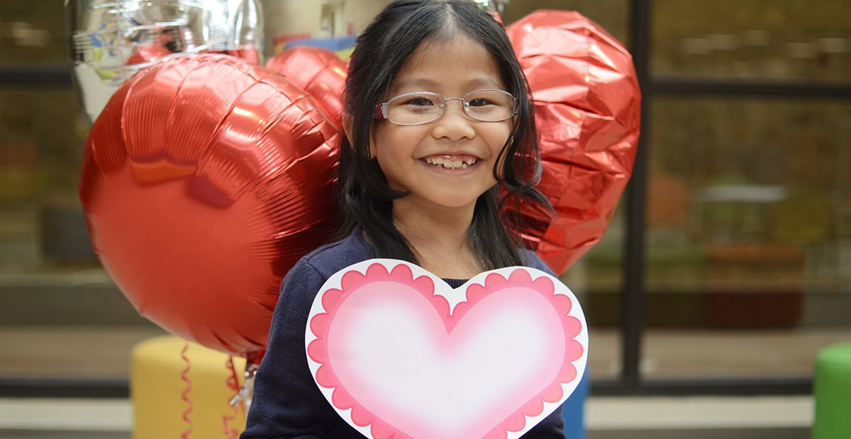 Texas Scottish Rite Hospital for Children patient surrounded by heart balloons