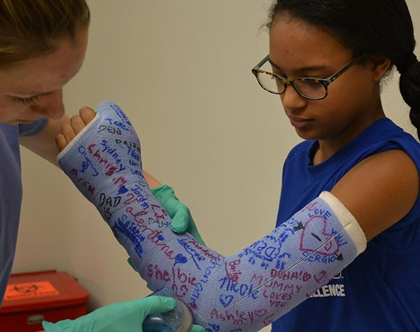 Nurse removing cast for arm fracture on young girl at Texas Scottish Rite Hospital for Children