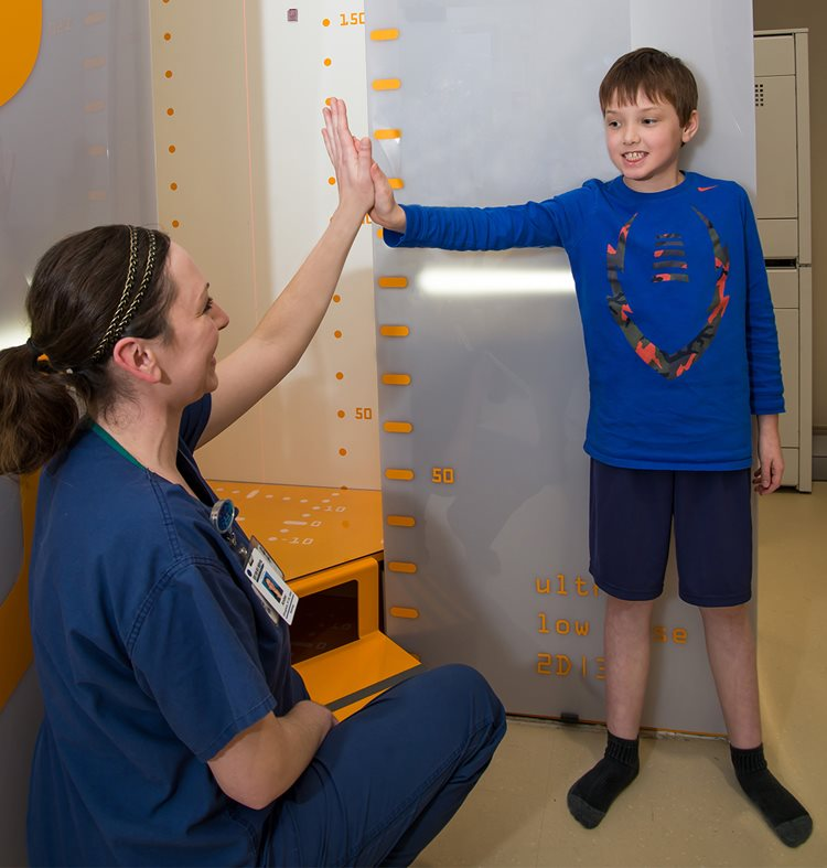 Radiology nurse high-fiving patient after X-rays were taken at Texas Scottish Rite Hospital for Children