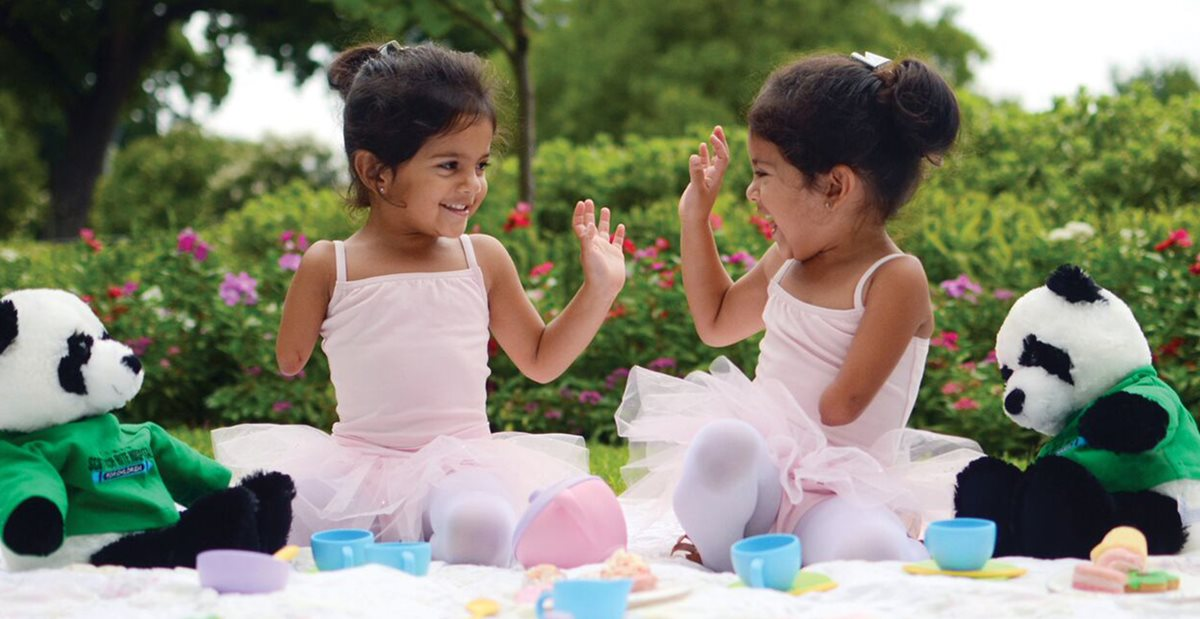 Twins with hand disorders play in the grass dressed as ballerinas