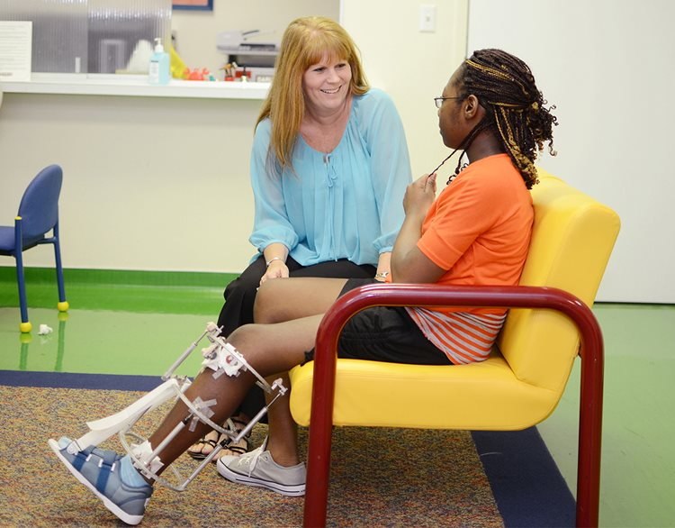 Pediatric psychologist talking with patient after surgery on leg injury at Texas Scottish Rite Hospital for Children