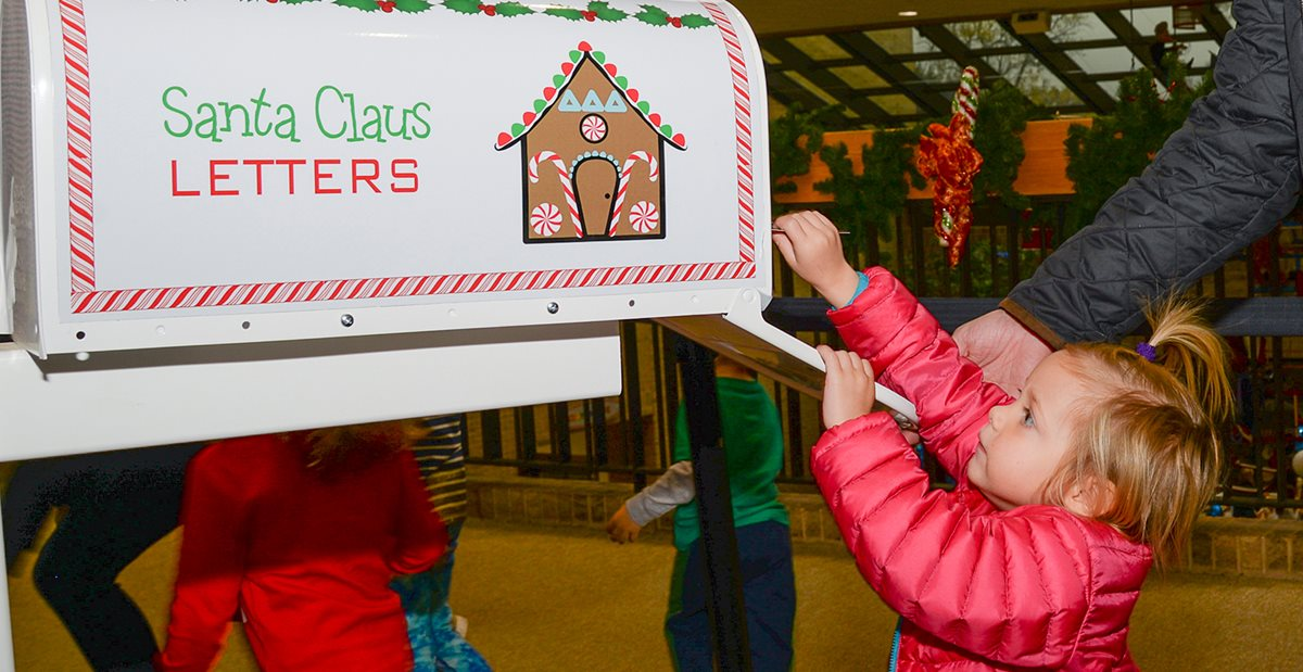 Child putting letter to Santa in mailbox at Cookies & Castles event benefiting Texas Scottish Rite Hospital for Children