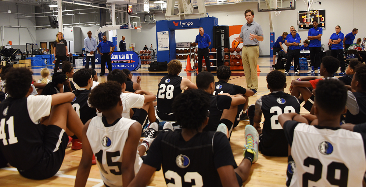 Dr. Ellis and other staff talking to participants of the Mavs Academy combine.