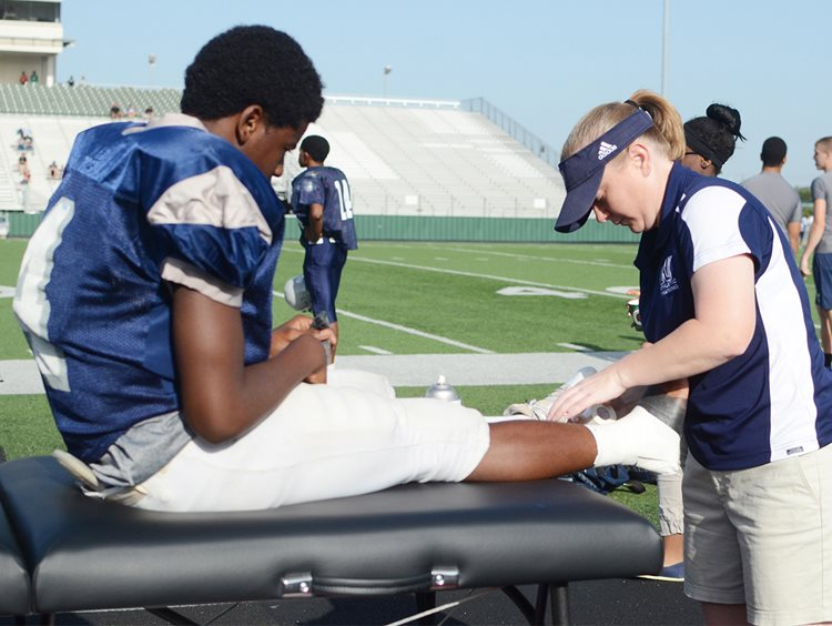Athletic trainer wrapping football player's ankle with tape to prevent athletic injury