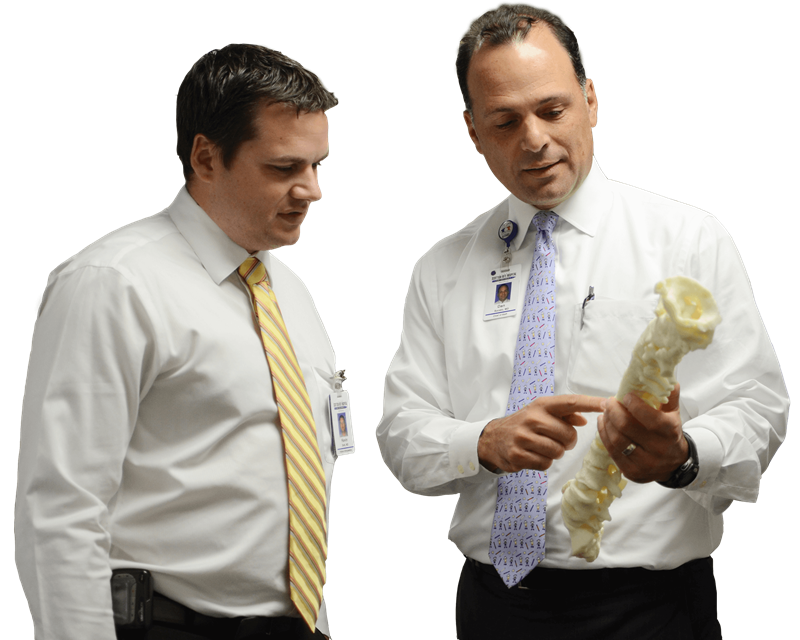 Orthopedic spine surgeon using a model spine to train another doctor at Texas Scottish Rite Hospital for Children